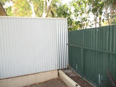 Straighten out neighbours leaning fence and install frame/tin to enclose gap.